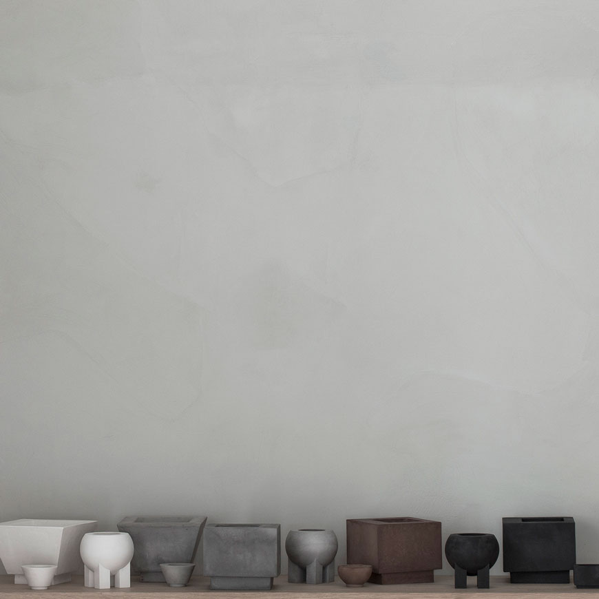 A selection of white, grey, brown and black ceramics against a textured grey wall, created by ceramist Laurie Poast.