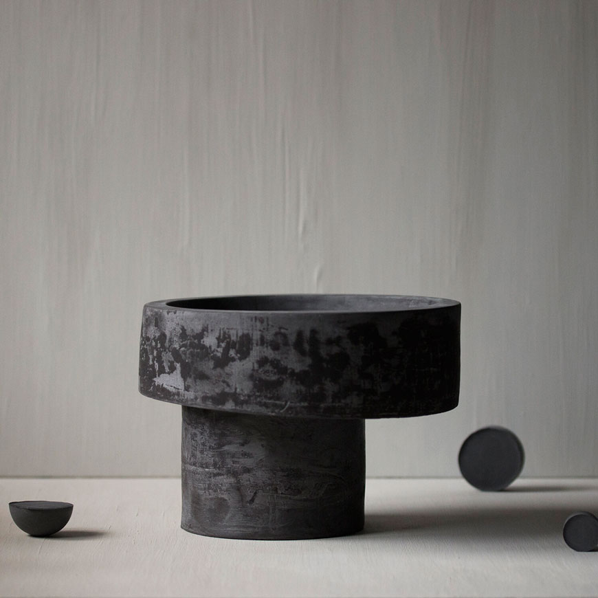 Asymmetric black ceramic Pedestal bowl styled against a textured grey backdrop.