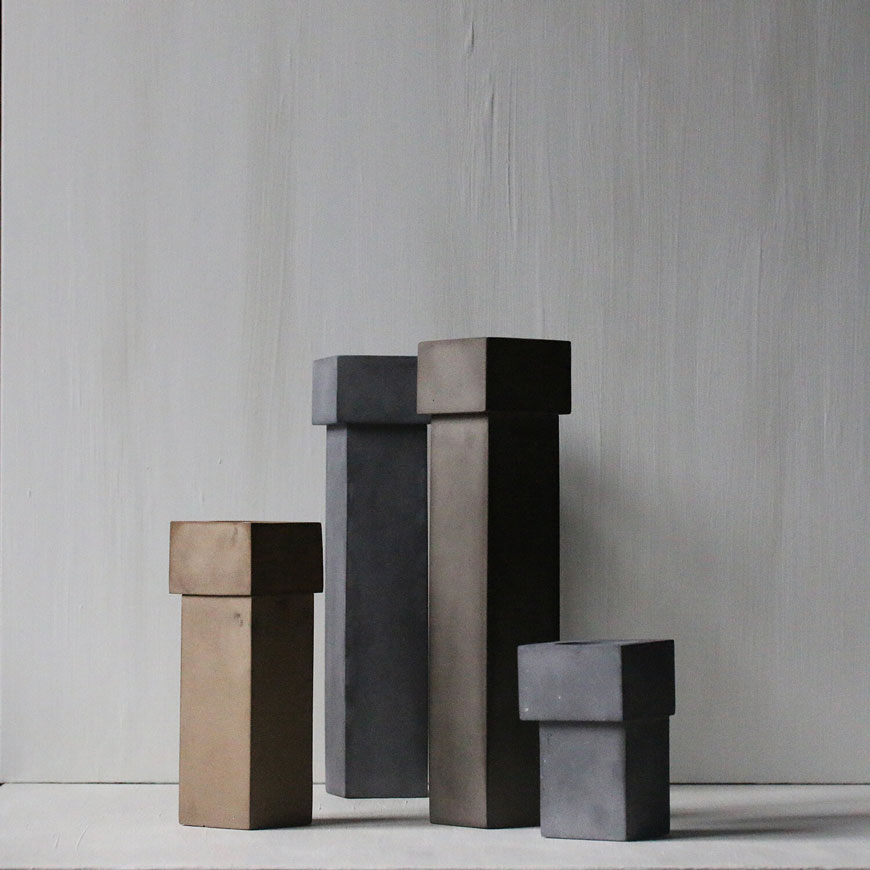 A small grouping of block shaped Brutalist ceramic candleholders against a textured grey wall.