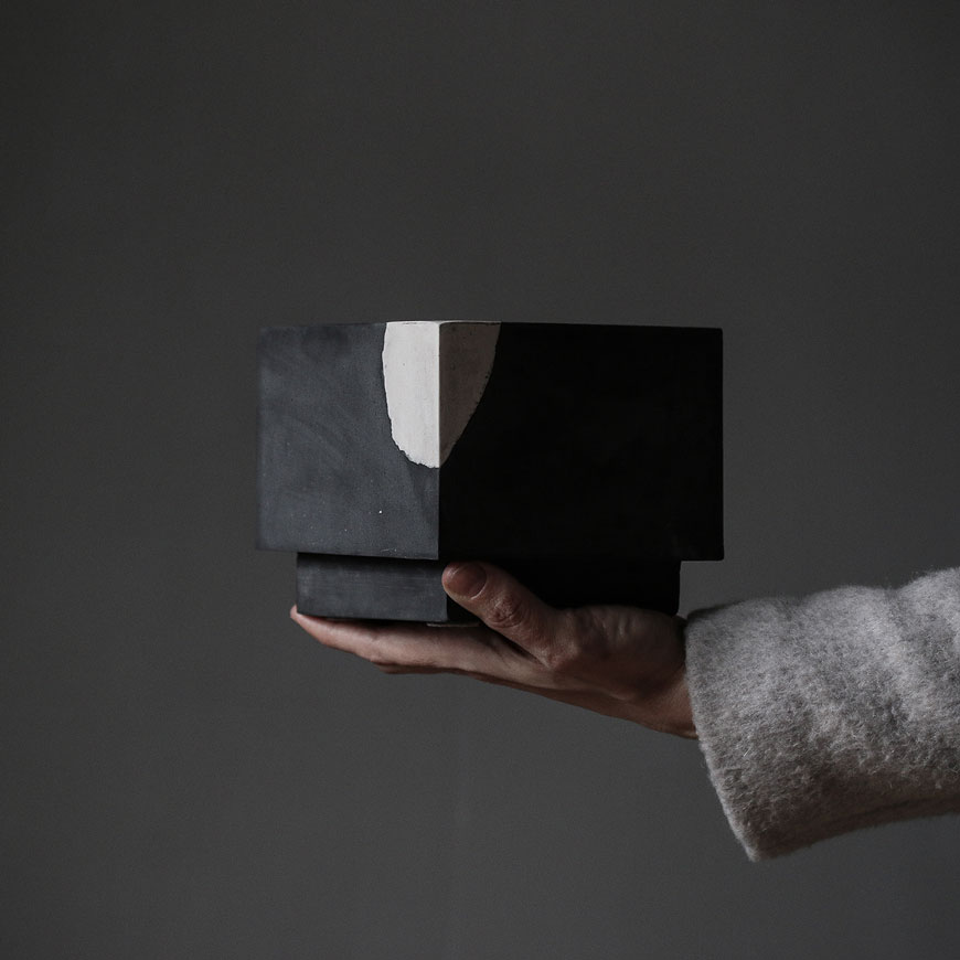 A black and white Cuboid pot, held by the hand of American-Scandinavian artist Laurie Poast.