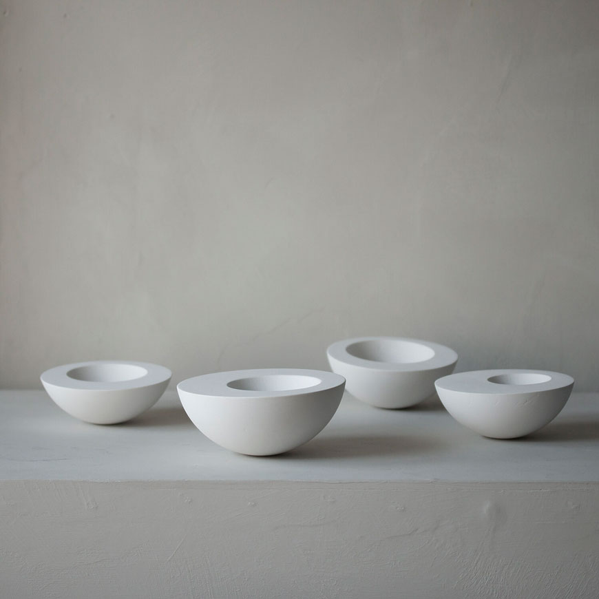Beautiful and delicate smooth white ceramic bowls with scooped out centres, against a neutral textured backdrop.