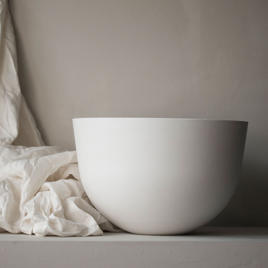 A serene and smooth pale white ceramic bowl styled against a swathe of white linen and a textured neutral wall.