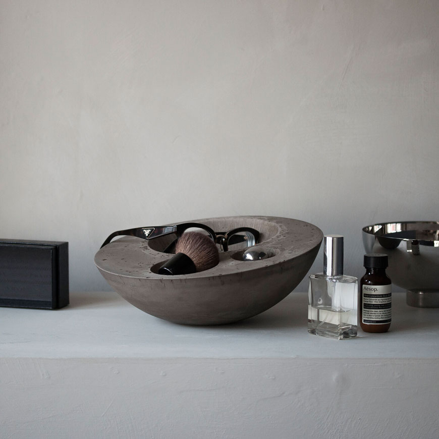 A mid-grey Valet bowl sits on a bathroom shelf, holding a pair of thick framed glasses and a shaving brush along side perfumes and toiletries.
