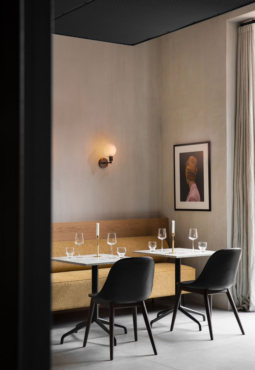 Inside the elegant and minimal restaurant at The Audo in Copehagen, featuring a mustard yellow Eave sofa and Walker wall light from the MENU Connected Spaces collection for 2020.