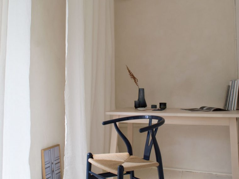 The limited edition CH24 Wishbone chair in navy blue lacquer, designed by Hans J. Wegner inside a warm, minimal workspace with limewashed walls and white floorboards.