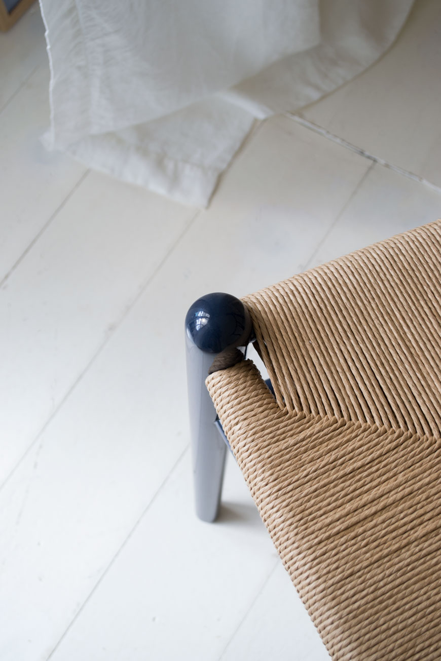 A detail shot of the woven paper cord seat of the CH24 Wishbone chair with glossy Navy blue finish.