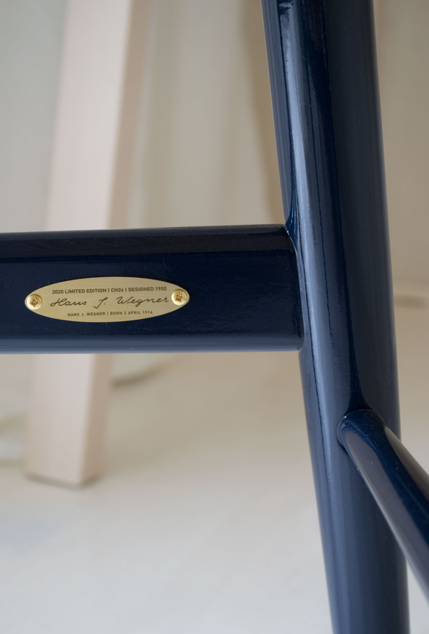 A detail of the brass plate inside the frame of the limited edition 2020 CH24 Wishbone chair in high gloss navy, designed by Hans J. Wegner.