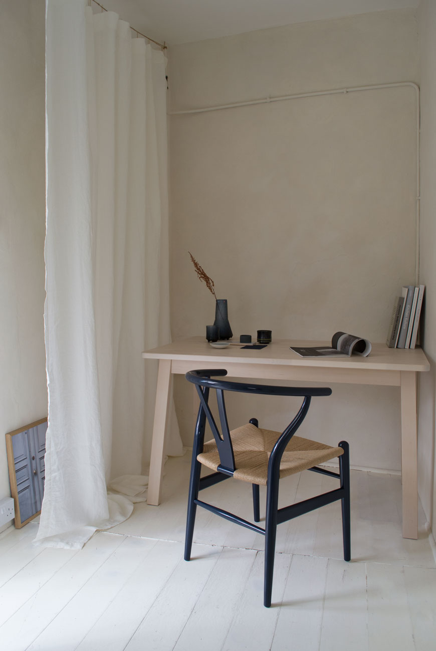 A warm, minimalist home office with limewashed walls and an inky blue Hans J. Wegner Wishbone chair.