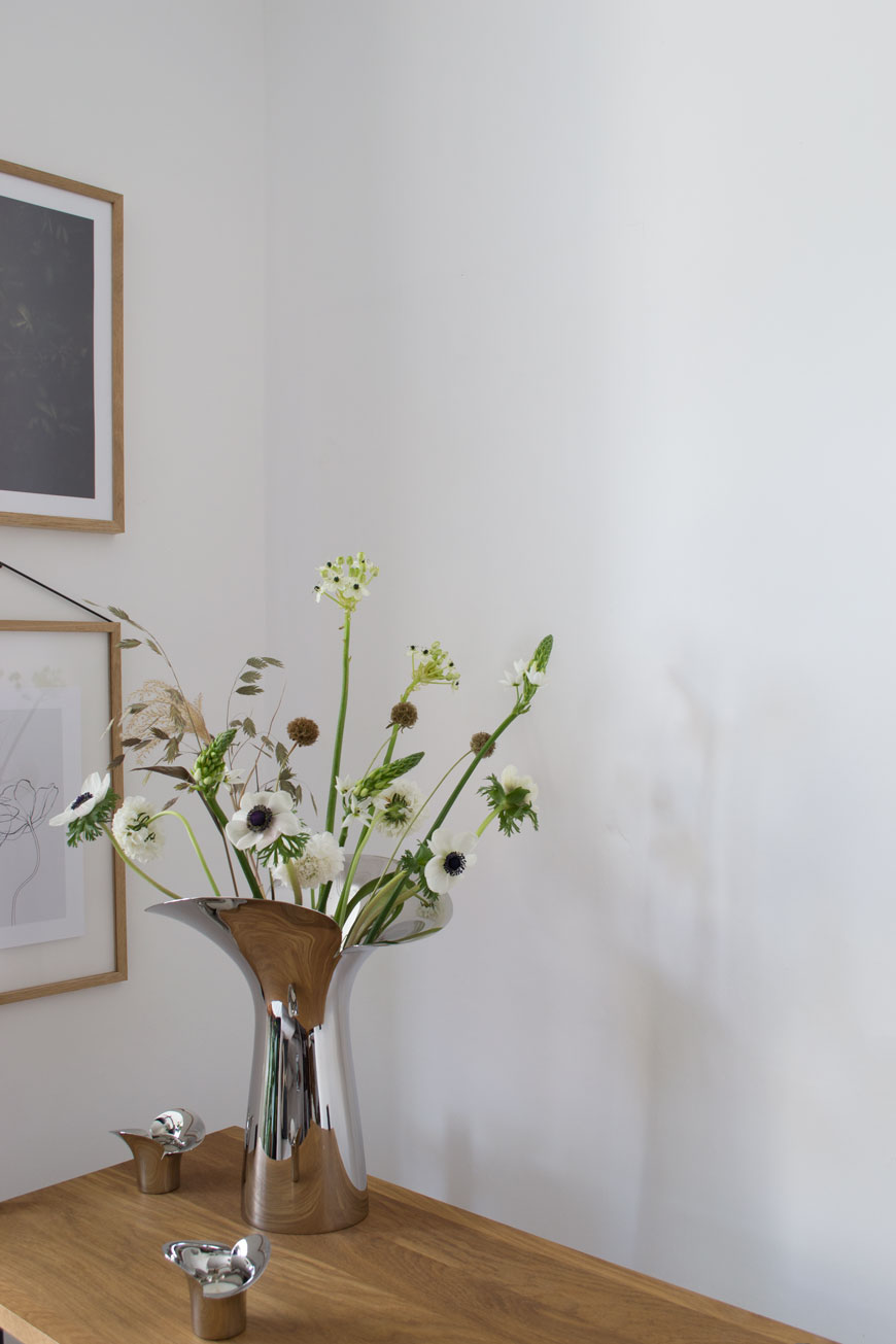 The poetic and sculptural Bloom Botanica vase collection by Georg Jensen typifies the elegance of timeless Scandinavian design, styled with white spring flowers in a minimal white living room.