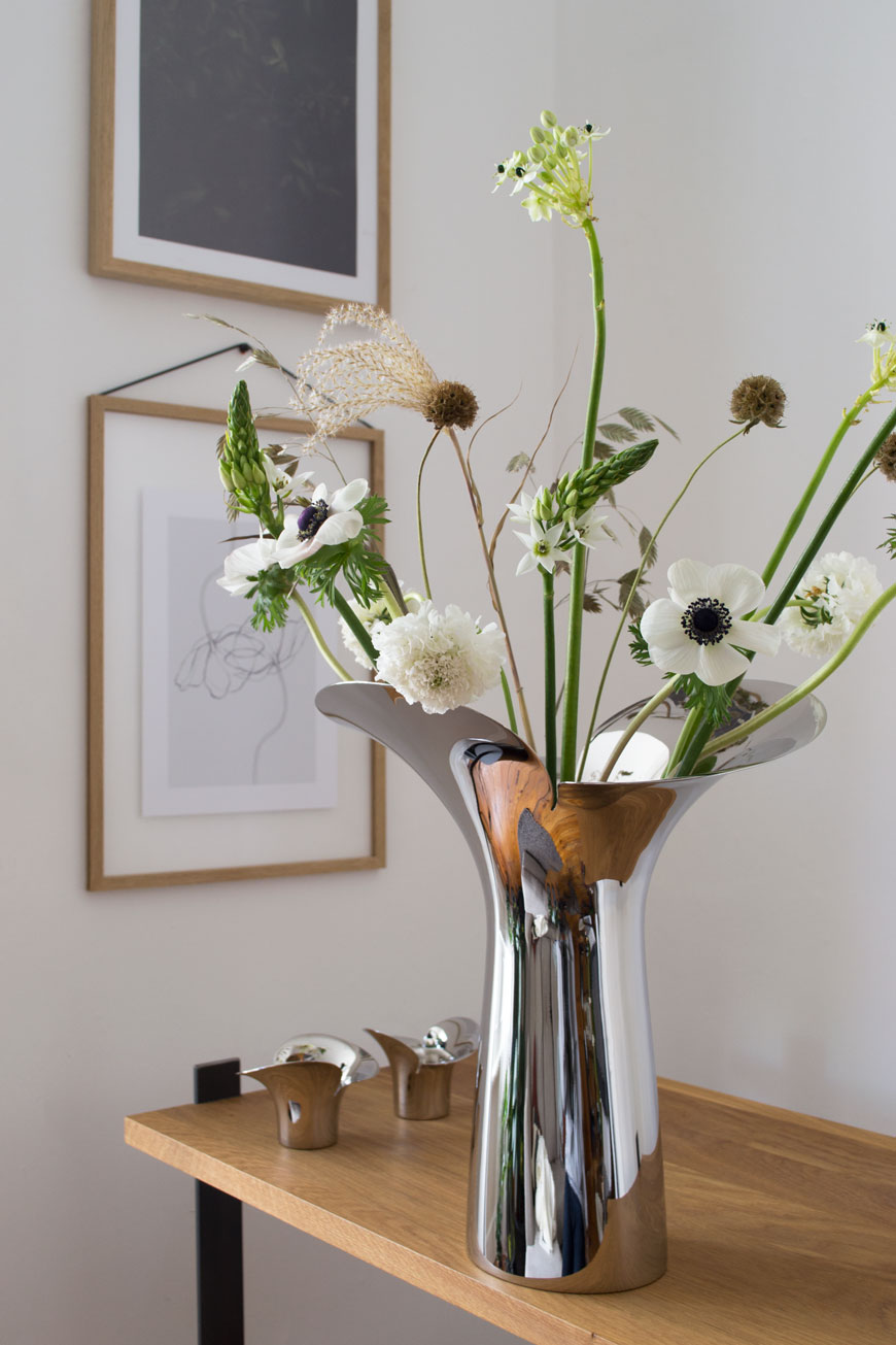 Elegant, fresh white spring flowers styled with textural grasses and seed heads in the new, sculptural Bloom Botanica vase, designed by Helle Damkjær for Georg Jensen.