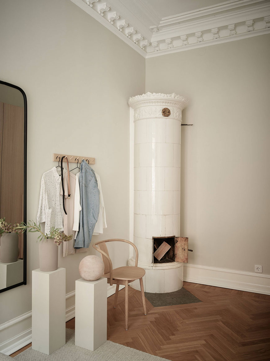 An original white tiled wood burner in the corner of an 1800s Gothenburg apartment, decorated with warm neutral tones