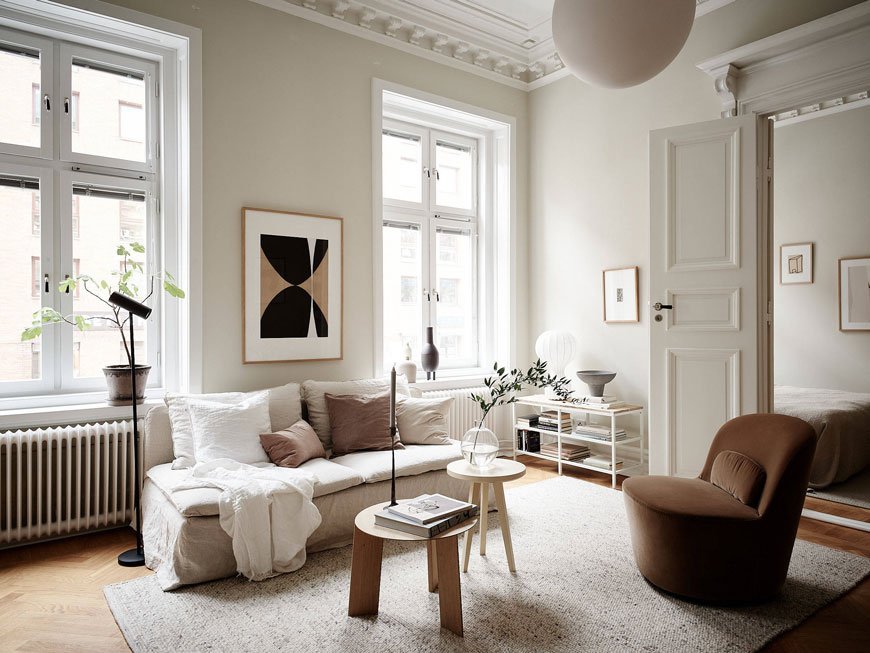 Inside a turn of the century Gothenburg apartment decorated with soft grey walls and warm neutral tones.
