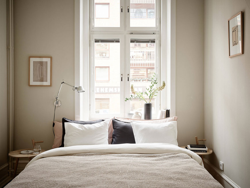 A cosy bed sits in front of a tall window inside a minimal bedroom painted with soft grey walls and minimal art.