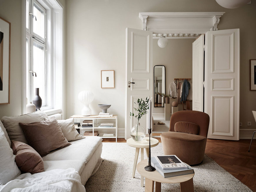 A curvy rusty pink velvet lounge chair sits opposite a linen sofa in the soft grey living room of an 1800s Gothenburg apartment, styled with Nordic design.