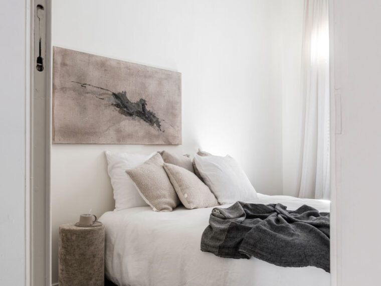 Looking into a minimal white bedroom inside Maison Jackie, Antwerp with contemporary abstract art above the bed and herringbone parquet floors.