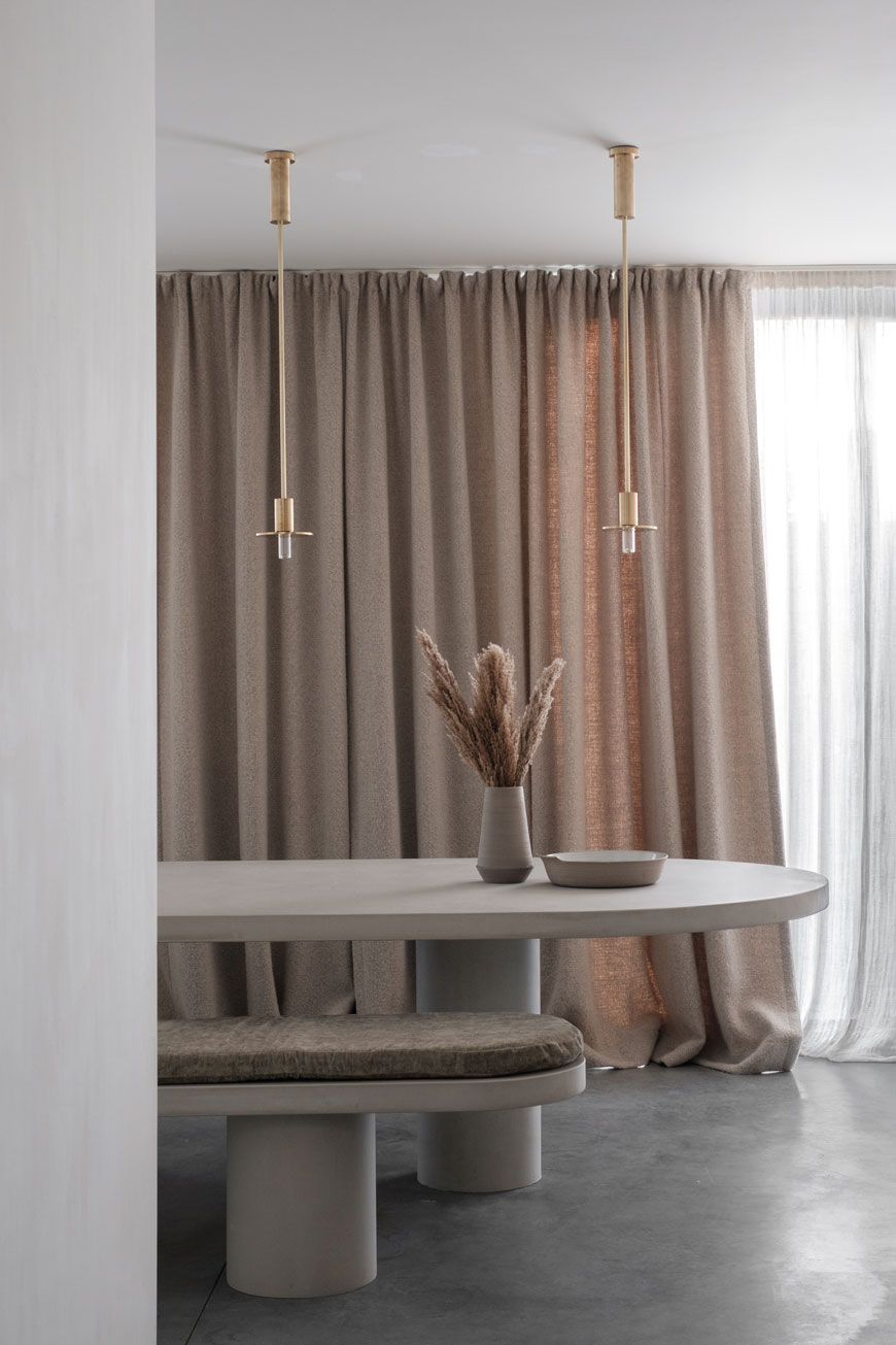 Full height natural linen curtains provide a contrast against a polished concrete floor in the kitchen dining room at Maison Jackie, Antwerp.